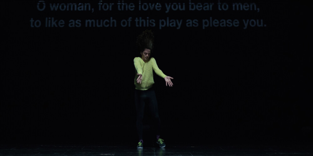 Dansare i gul tröja, bakom projiceras text ur Shakespeares pjäs As you like it.