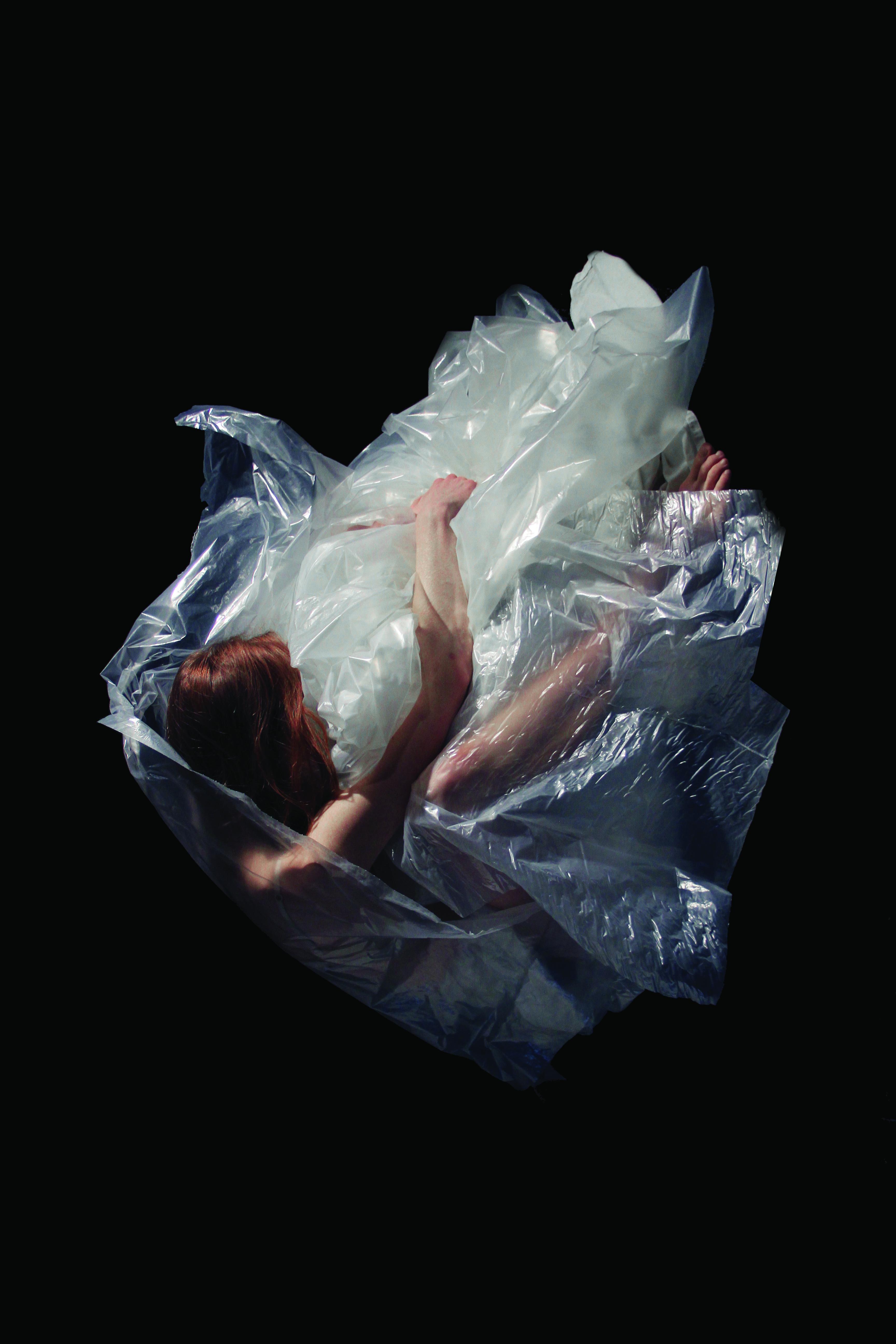 Naken kvinna rullar runt i plast.